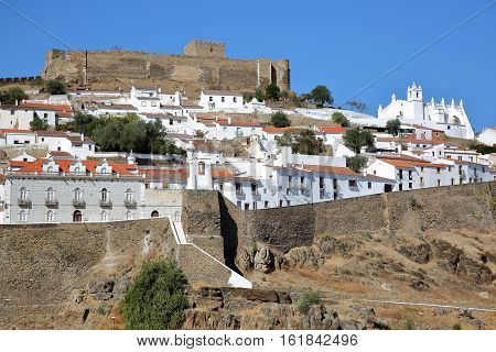 MERTOLA, PORTUGAL: View of the fortified village from the opposite bank of the river Guadiana with the castle and the Matriz Church in the background