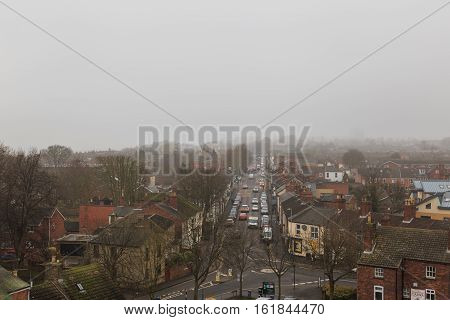 LINCOLN ENGLAND - DECEMBER 15: Traffic on Burton Road Lincoln UK. In fog. View from high on the castle wall. In Lincoln England. On 15th December 2016.
