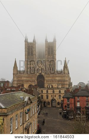 LINCOLN ENGLAND - DECEMBER 15: Lincoln Cathedral viewed from castle wall in fog. In Lincoln England. On 15th December 2016.