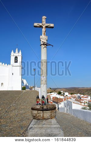 MERTOLA, PORTUGAL: The Matriz Church  (former Mosque of Mertola) with a religious cross in the foreground