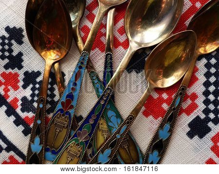 Tea and dessert spoons on a white  flax tablecloths. The handle color enamel and a view of the tower. Retro. Closeup.