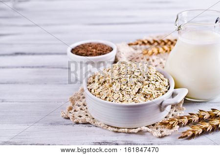 Dry oat flakes with flax seeds and milk on a light wooden background. Selective focus.