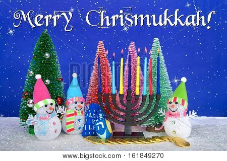 Menorah and red pink green pine trees with snowman on faux snow blue background white dots and stars. Christmas and Hanukkah together. Multi faith celebration. Merry Chrismukkah