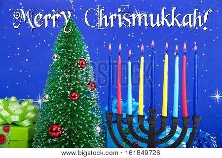 Miniature Christmas tree with presents next to Jewish menorah celebrating Hanukkah. Multi faith families celebrate both. Merry Chrismukkah