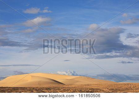 Sand dunes and clouds on blue sky background. Mui Ne Vietnam