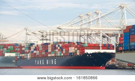 Oakland CA - December 13 2016: Cargo Ship YM ULTIMATE loading at the Port of Oakland the fifth busiest port in the United States.