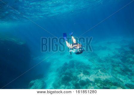 Young female apnea swims in deep waters of the popular Similan Islands in Thailand, Andaman Sea.
