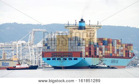 Oakland CA - December 13 2016: Multiple tugboats push and pull cargo ship GERD MAERSK to turn the vessel prior to docking at the Port of Oakland.