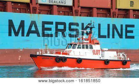 Oakland CA - December 13 2016: Pilot vessel GOLDEN GATE departing GERD MAERSK after picking up a harbor pilot. As a ship pulls into port a Harbor Pilot boards and guides it safely to shore.