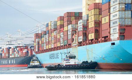 Oakland CA - December 13 2016: Tugboats REVOLUTION and DELTA CATHRYN assist cargo ship GERD MAERSK maneuver into the Port of Oakland.