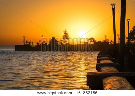 Sunset on Avenida Costanera Rafael Obligado in front of Buenos Aires aeroparque international airport - Romantic travel concept with sun reflection on the water of Rio de la Plata waterfront