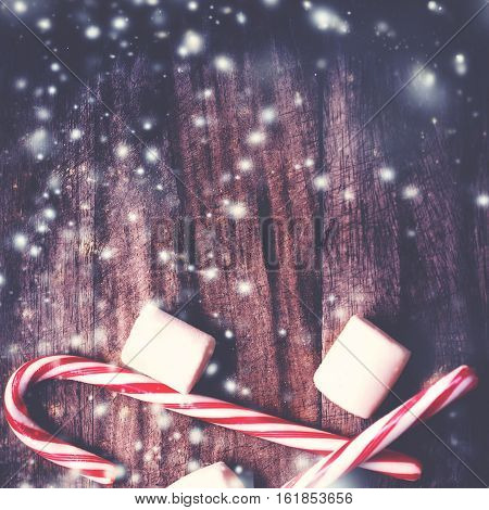 Christmas Card with striped hard candy cane and marshmallows over wooden background. Christmas candy