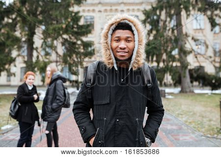 Portrait of a smiling afro american man student with backpack standing outside at the university campus