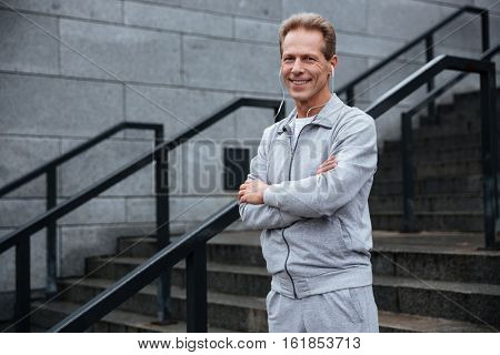 Runner in gray sportswear and headphone standing on stairs with arms crossed and looking at camera. Side view