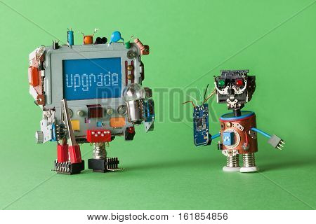 Upgrade computer concept. Handyman technician robot with circuit in hand and monitor computer robotic character, warning message on blue screen. green background
