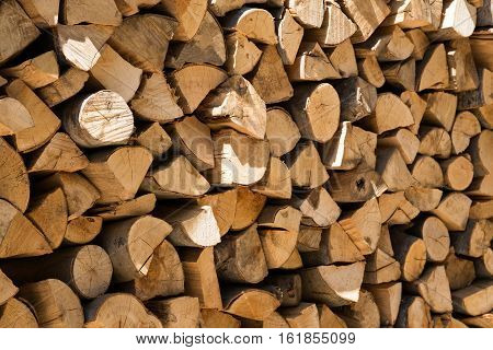 Background texture of a neatly stacked woodpile of dried cut and split logs for providing winter heating and fuel in a full frame and diagonal view