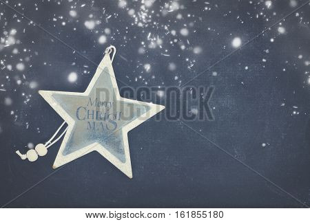 Merry Christmas star on black wooden background with copy space and snow