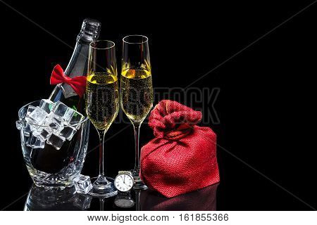 Bottle of champagne in an ice bucket with wineglasses and gift in sack