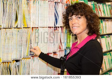Woman Buying And Choosing A Book Or Card In A Shop Center