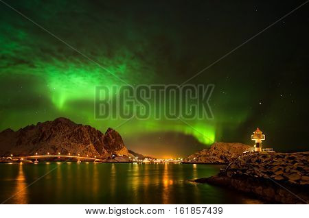 Aurora Borealis over lighthouse in Reine, Lofoten, Norway