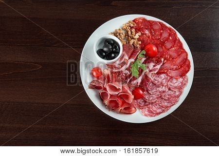 Salami love. Top view of a delicious salami and ham meat plate at the restaurant copyspace