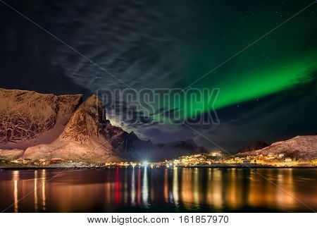 Aurora Borealis behind clouds over Reine and snowy mountains Lofoten