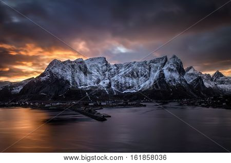 Reine village in winter evening with snowy mountains and colorful clouds in background Lofoten