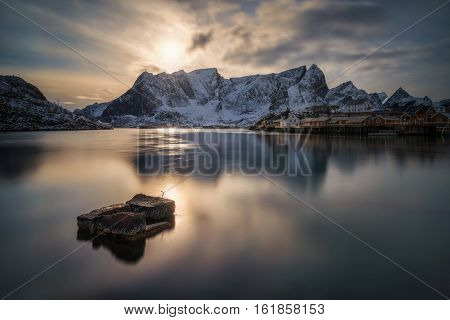 Sakrisoya island and Reine village at cold sunset with snowy mountains in background Lofoten