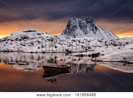 Fishing boat in fjord among snowy mountains Lofoten
