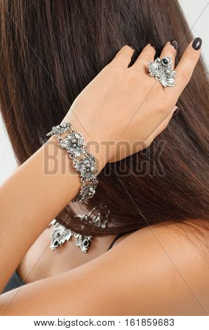 close-up fashion portrait of Diamond ring necklace bracelets earrings sensual tan skin girl in black dress and black nail in jewelry shop hand with ring over her neck