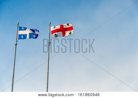 Montreal and Quebec flags waving over blue sky