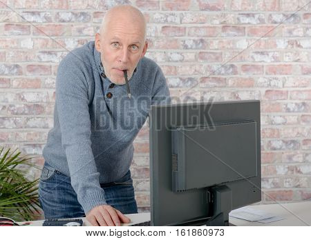 handsome mature man using computer at office
