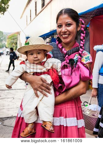 OAXACA, MEXICO-DEC 10, 2015: Beautiful lady and boy celebrating Day of the Virgin of Guadalupe (Dia de la Virgen de Guadalupe) on Dec 10, 2015 . Oaxaca, Mexico. It is a popular Catholic feastival