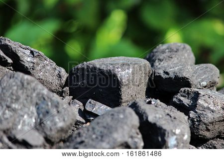 Black shiny faceted pieces Charcoal lies on a background of green grass.