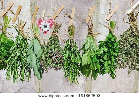Various fresh herbs and a hand-sewn heart of fabric hanging on a cord