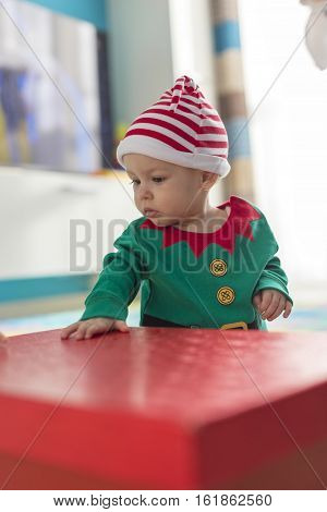 child in a Santa's helper elf costume with red box