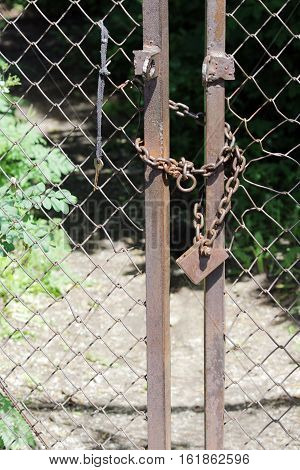 metal lock closes the gate with a chain and key is hanging near.