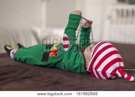 Child in Santa's helper elf costume lying and playing with beads