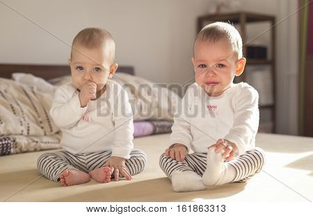 crying baby sitting on a bed with his twin