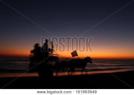 Horse cart running in sunset on the beach