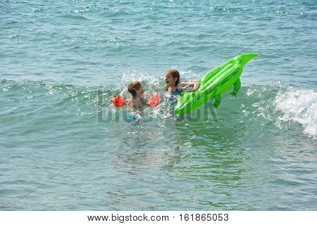 two children swim on a crocodile - air bed in the sea waves