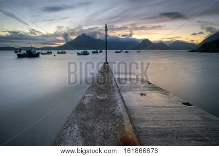Elgol pier in late evening with Cuillin Mountains in background Isle of Skye Scotland