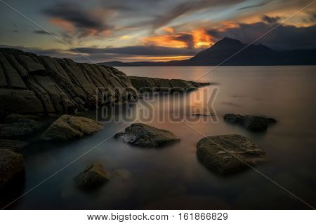 Rocky coastline of Loch Scavaig with Cuillin Mountains in background Isle of Skye Scotland