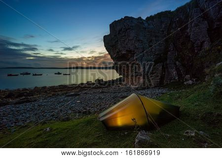 Tent pitched on Elgol coastline at sunset with boats and mountains in background Isle of Skye Scotland