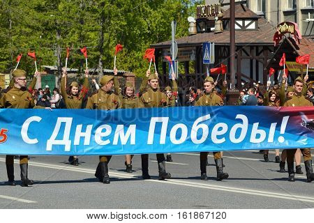 People in military clothes bear a banner