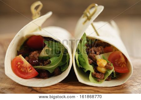 fresh homemade tortilla wrap sandwiches with beef and vegetables on olive board, closeup photo with shallow focus