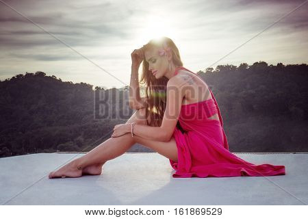 Summer outdoor portrait of young pretty elegant girl posing at roof at sunset
