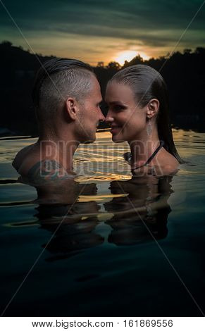 Romantic sensual couple alone in infinity swimming pool over beautiful tropical and sunset sky background