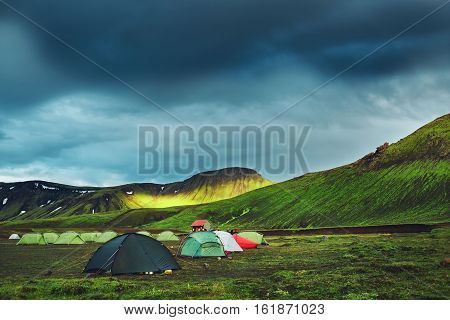 Travel to Iceland. Beautiful Icelandic landscape with mountains, sky and clouds. Trekking in national park Landmannalaugar. Rainy Evening in Camping near Alftavatn lake.