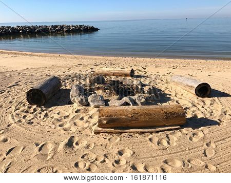 manmade log fire pit on the beach